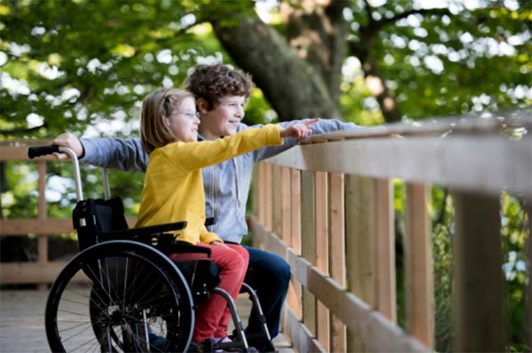 Young boy and girl in a wheelchair looking over a wooden railing