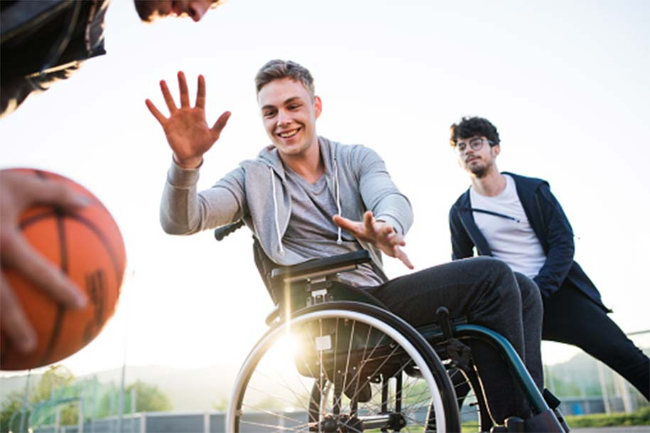 Young man in a wheelchair playing basketball with friends